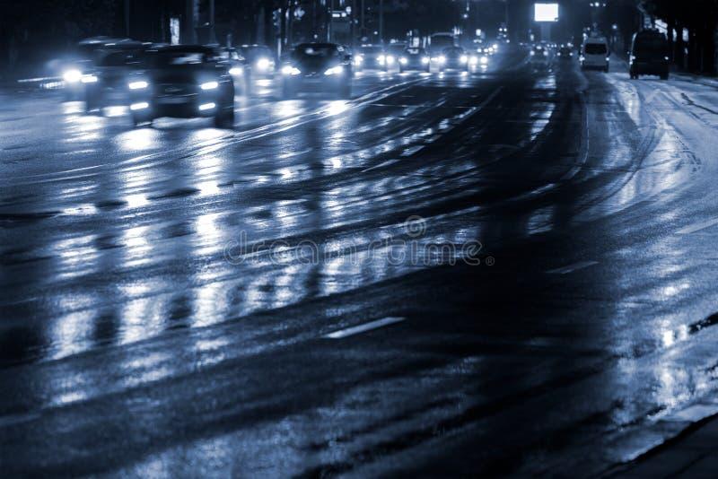 El coche enciende el reflejo en camino mojado después de lluvia Movimiento enmascarado fotos de archivo libres de regalías