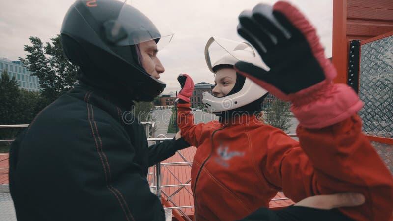 El coche masculino da instrucciones a una muchacha del skydiver antes de volar en el túnel de viento imagen de archivo libre de regalías