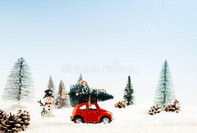 El coche modelo fundido a troquel lleva el árbol de navidad en una capa nevosa y del invierno foto de archivo