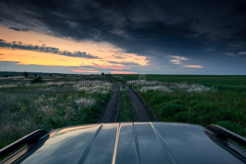El coche monta en un camino de tierra en el campo, la puesta del sol hermosa con la hierba salvaje, la luz del sol y las nubes os imagen de archivo