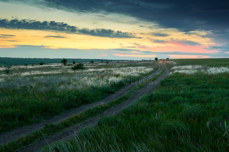 El coche monta en un camino de tierra en el campo, la puesta del sol hermosa con la hierba salvaje, la luz del sol y las nubes os fotos de archivo libres de regalías