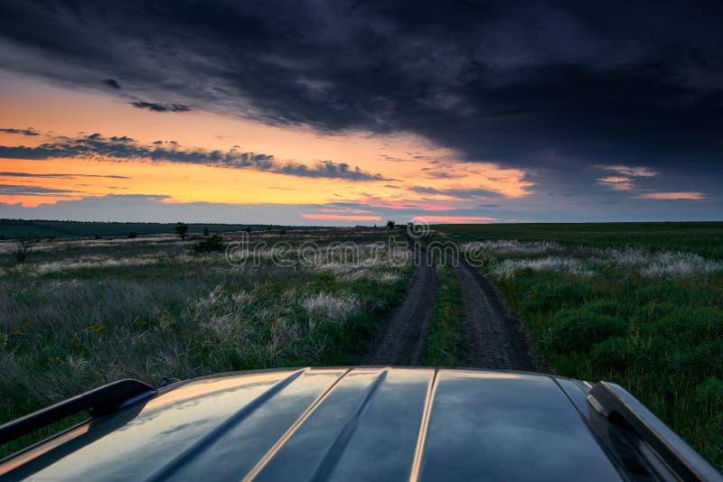 El coche monta en un camino de tierra en el campo, la puesta del sol hermosa con la hierba salvaje, la luz del sol y las nubes os fotografía de archivo