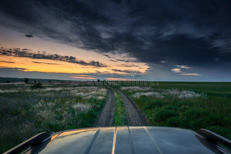El coche monta en un camino de tierra en el campo, puesta del sol hermosa con foto de archivo