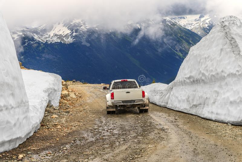 El coche monta en un mojado, pedregoso, suciedad, camino de la montaña, entre el snowdrif imagen de archivo