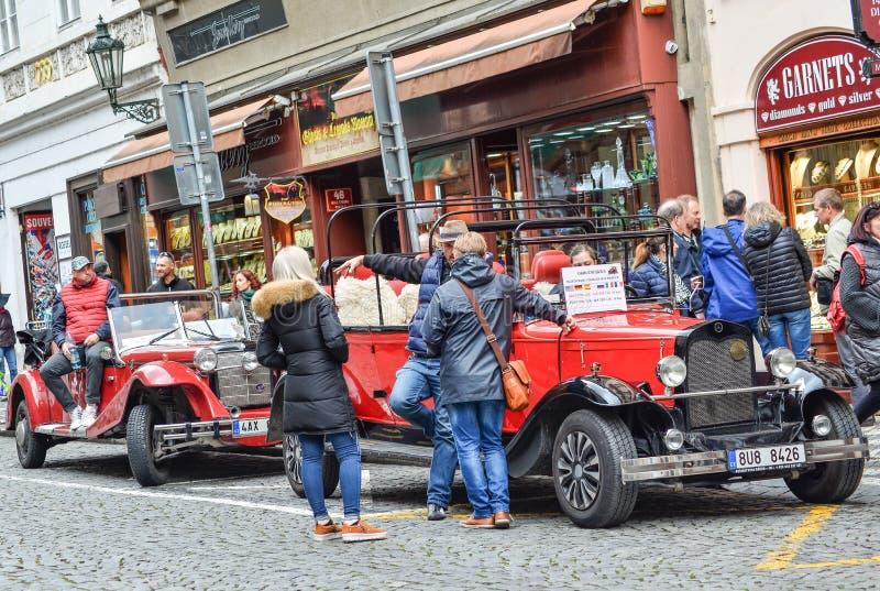 El coche retro blanco y rojo hermoso con los turistas monta a lo largo del camino, Praga, República Checa Coche del vintage para  fotografía de archivo libre de regalías