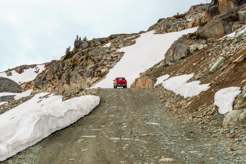 El coche rojo monta a lo largo de una carretera nacional en las montañas rocosas foto de archivo