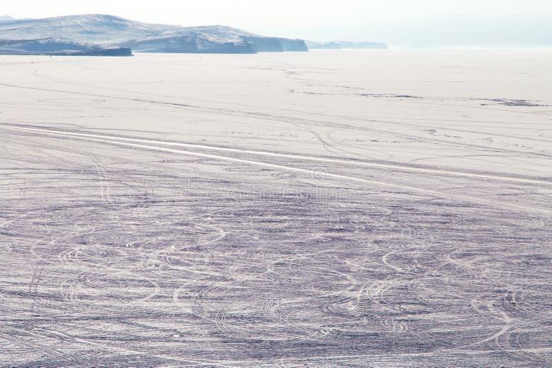 El coche se arrastra en la superficie congelada del lago cubierta con nieve Lago Baikal fotografía de archivo