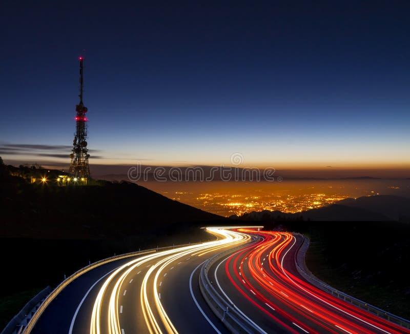El coche se enciende en la noche hacia la ciudad y la antena de las comunicaciones imagen de archivo