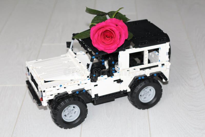 El coche SUV del juguete lleva una rosa roja real fotografía de archivo