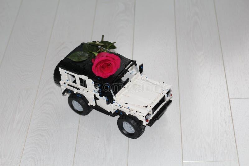 El coche SUV del juguete lleva una rosa roja real imagen de archivo libre de regalías