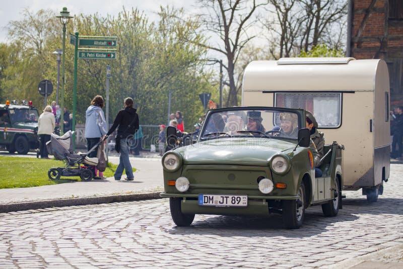 El coche trabante alemán con el remolque conduce en una calle imagenes de archivo