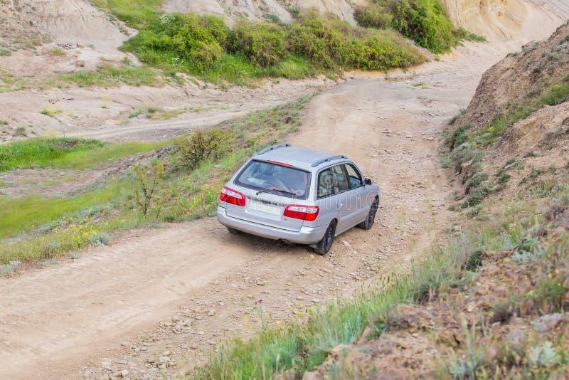 el coche va abajo del camino de tierra de la montaña fotografía de archivo libre de regalías