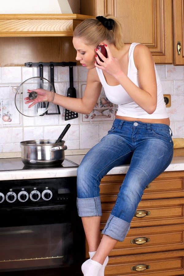 El cocinar atractivo joven de la mujer fotografía de archivo