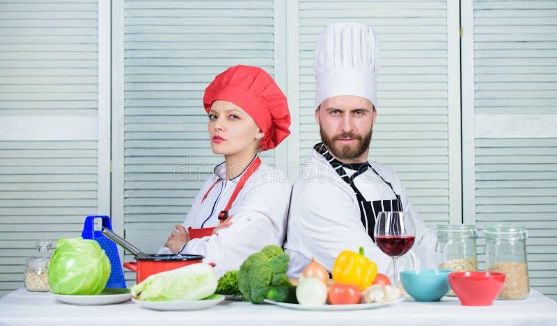 El cocinar con su c?nyuge puede fortalecer relaciones Socios culinarios de la mujer y del hombre barbudo El ?ltimo cocinar imagen de archivo