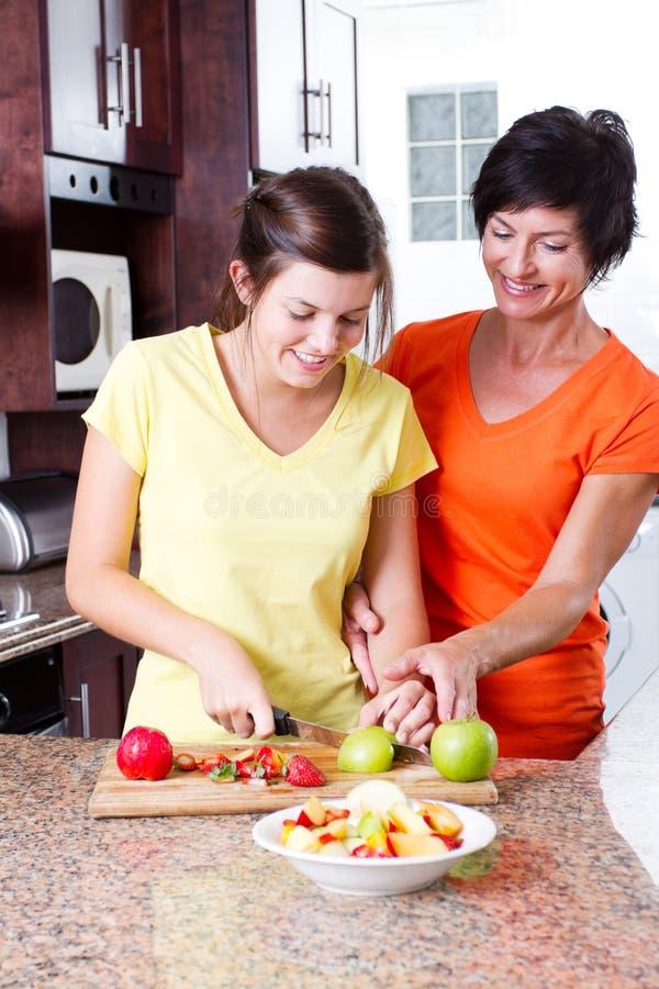 El cocinar de enseñanza de la hija de la madre imagenes de archivo