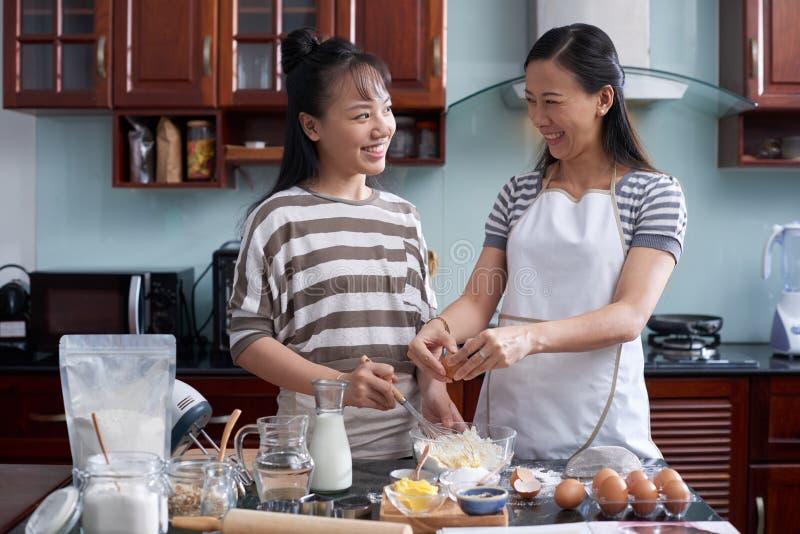 El cocinar de enseñanza de la hija de la madre fotografía de archivo