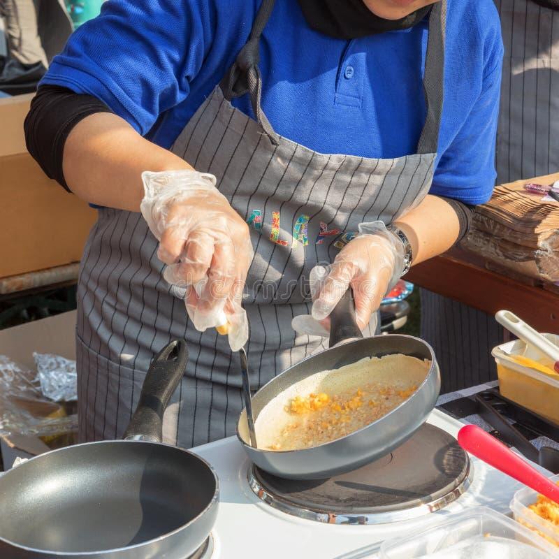 El cocinar de la comida de la calle, haciendo las crepes imagen de archivo libre de regalías