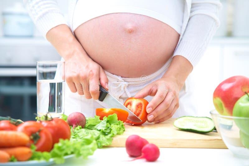 El cocinar de la mujer embarazada imagenes de archivo