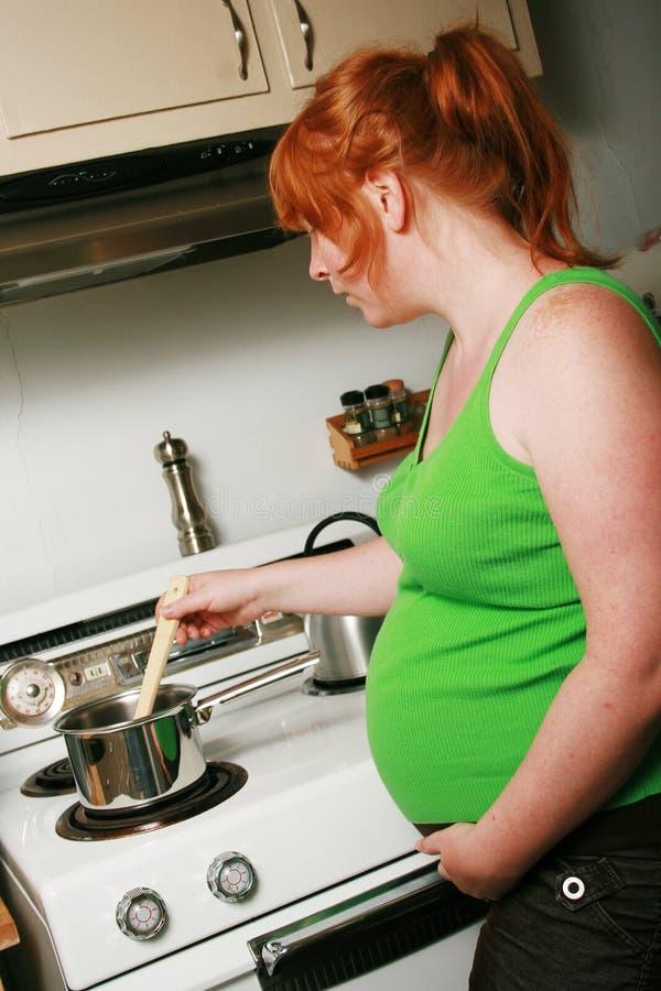 El cocinar de la mujer embarazada imágenes de archivo libres de regalías
