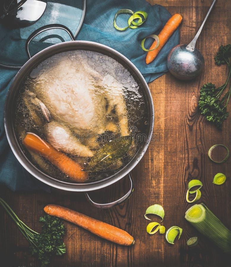 El cocinar de la sopa de pollo, pote con caldo de pollo y cucharón en el fondo de madera rústico oscuro con los ingredientes de l imagen de archivo libre de regalías