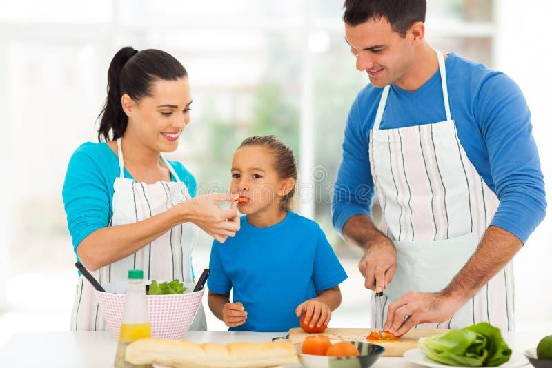 El cocinar de los padres de la prueba de la muchacha foto de archivo