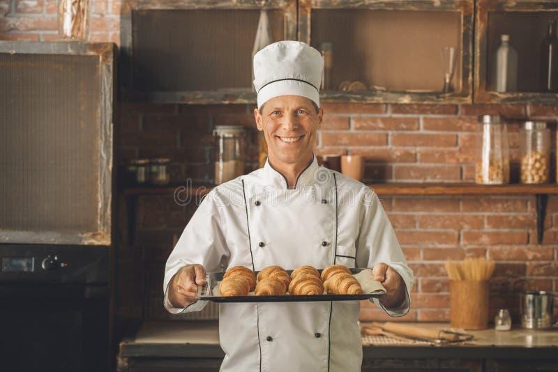 El cocinar del cocinero de la panadería cuece en el profesional de la cocina fotografía de archivo libre de regalías