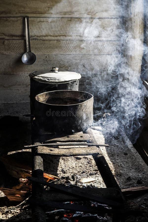 El cocinar en cazos en una estufa improvisada sobre un fuego foto de archivo libre de regalías