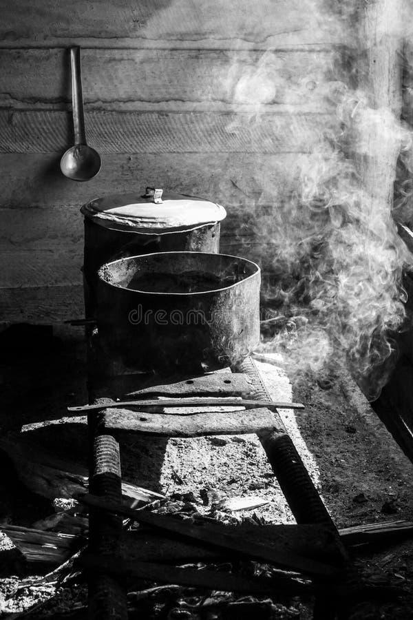 El cocinar en cazos en una estufa improvisada sobre un fuego fotos de archivo libres de regalías