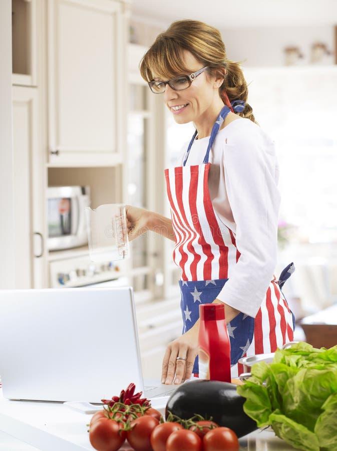 El cocinar feliz de la mujer imagenes de archivo
