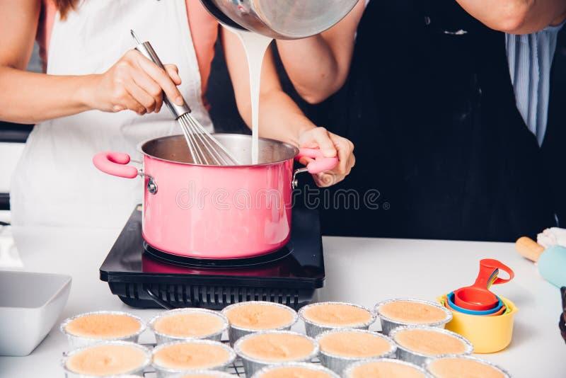 El cocinar hermoso de la mujer bate la pasta en manual del cuenco fotografía de archivo libre de regalías