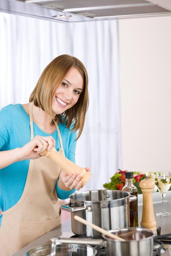 El cocinar - mujer feliz por la estufa en cocina fotografía de archivo