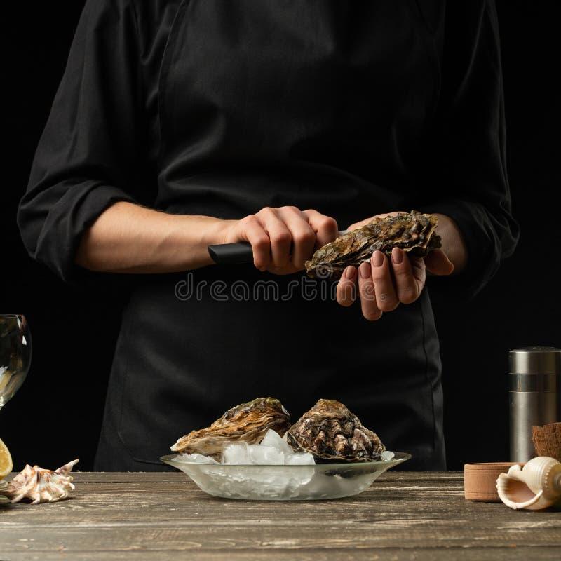 El cocinero abre el cuchillo y limpia la ostra cruda, en el fondo del vino blanco, de la lechuga, de los limones y de las cales fotos de archivo libres de regalías