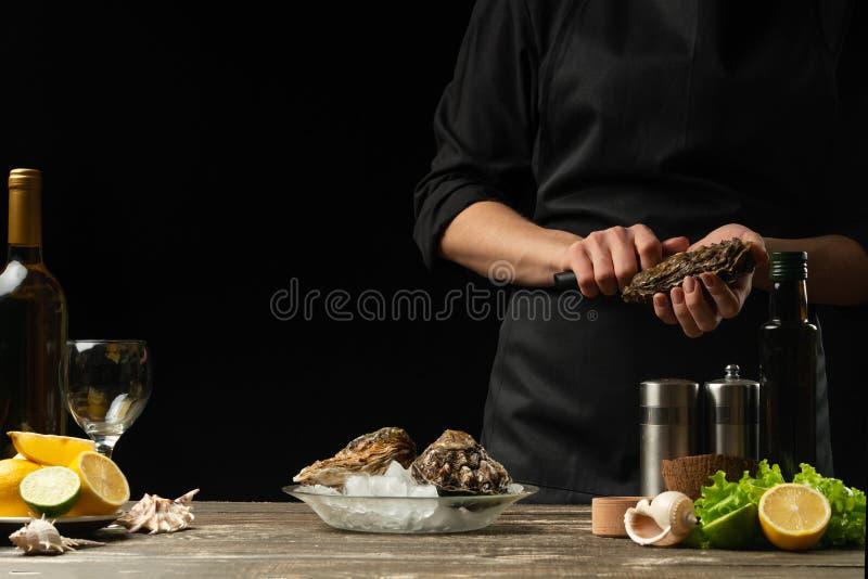 El cocinero abre el cuchillo y limpia la ostra cruda, en el fondo del vino blanco, de la lechuga, de los limones y de las cales C foto de archivo libre de regalías