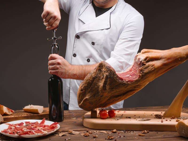 El cocinero abre una botella de vino Jamon, especias, tomates y anillos de cebolla tradicionales Jamón rebanado foto de archivo libre de regalías