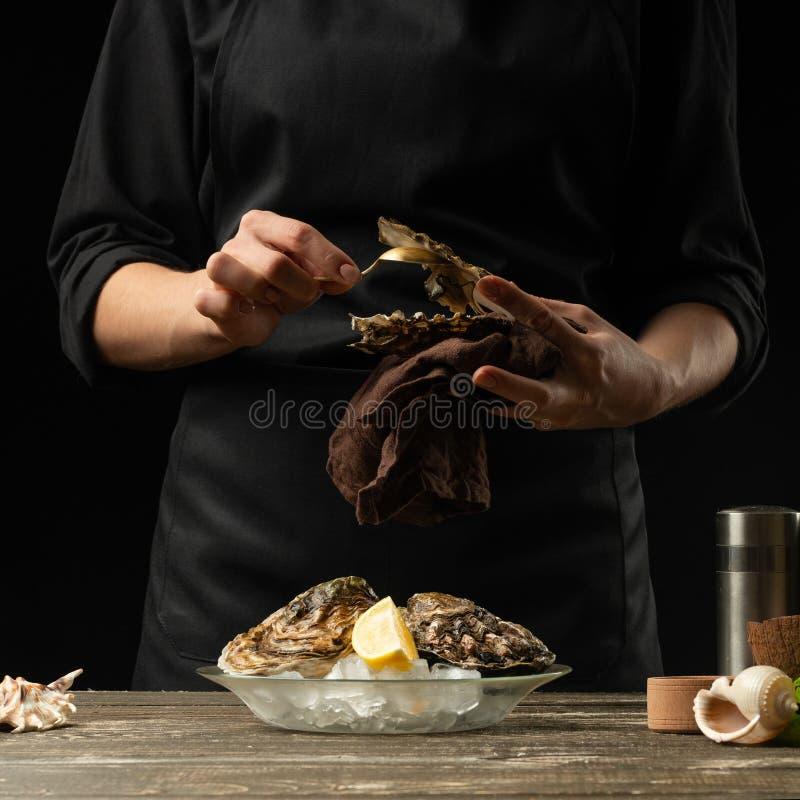 El cocinero abre y limpia la ostra cruda contra un fondo del vino blanco, de la lechuga, de los limones y de las cales imagen de archivo