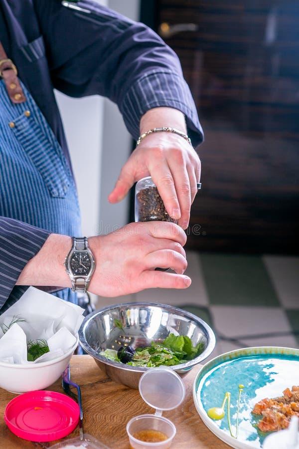 El cocinero adorna la ensalada con el pato rasgado, la calabaza picante y la salsa de la fruta cítrica Clase principal en la coci imágenes de archivo libres de regalías