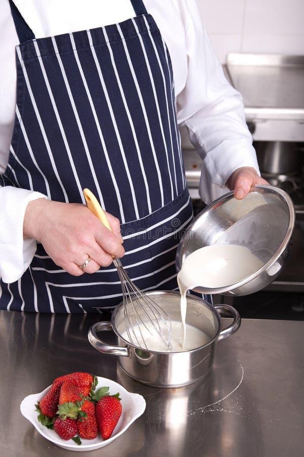 El cocinero agrega la leche en una cacerola foto de archivo libre de regalías