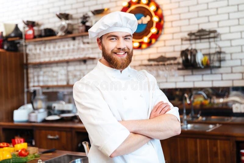 El cocinero alegre del cocinero que se colocaba con los brazos cruzó en la cocina foto de archivo