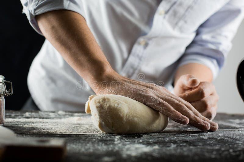 El cocinero amasa la pasta con la harina en la tabla de cocina imágenes de archivo libres de regalías