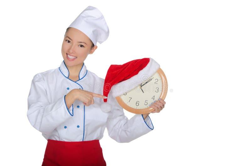 El cocinero asiático señala en el reloj con el sombrero de la Navidad imágenes de archivo libres de regalías