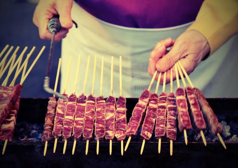 El cocinero cocina Arrosticini llamado carne en de lengua italiana una clase o imagenes de archivo