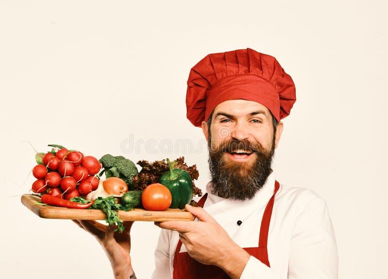 El cocinero con la cara alegre en el uniforme de Borgoña sostiene los ingredientes de la ensalada El cocinero lleva a cabo al tab fotografía de archivo libre de regalías