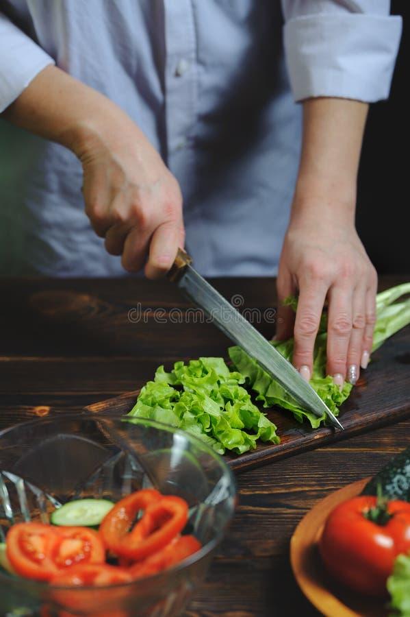 El cocinero corta con un cuchillo una ensalada vegetariana imagenes de archivo