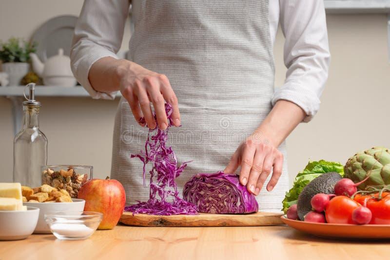 El cocinero corta la col púrpura para la ensalada, el concepto de comida sabrosa y sana, dieta, comida vegetariana, detox fotos de archivo libres de regalías