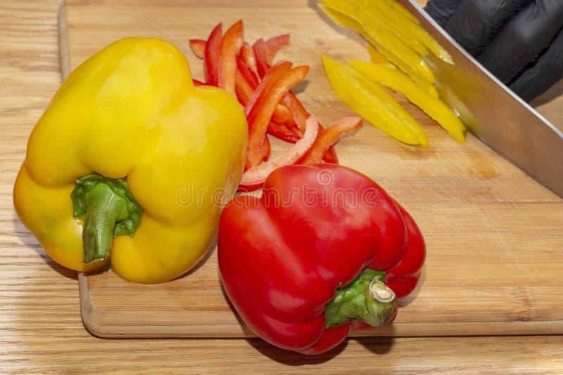 El cocinero corta las pimientas de la paprika en plato dietético vegetariano en guantes en una tabla de cortar de madera imagenes de archivo
