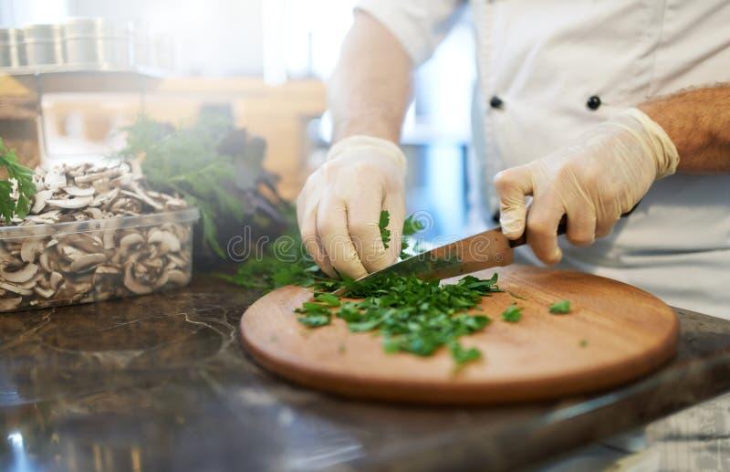 El cocinero corta los verdes fotos de archivo