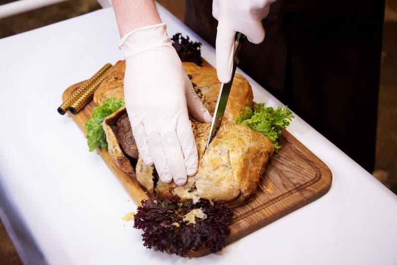 El cocinero corta el plato caliente cocinado en una bandeja en un restaurante fotografía de archivo
