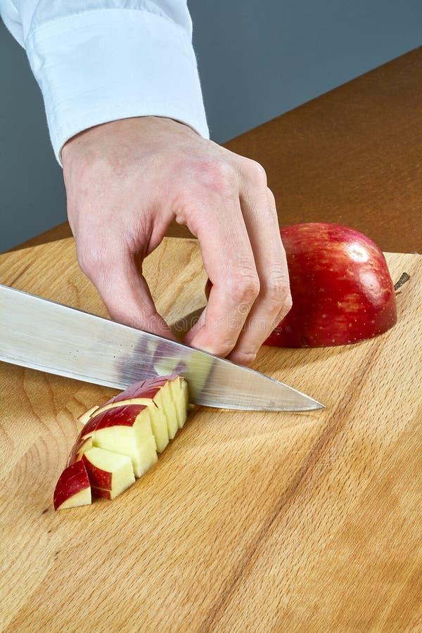El cocinero corta una manzana roja para cocinar el vino reflexionado sobre una colección completa de recetas culinarias imagenes de archivo