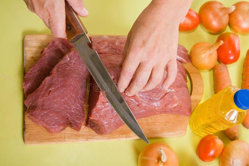El cocinero de F da la carne de vaca del corte imagen de archivo