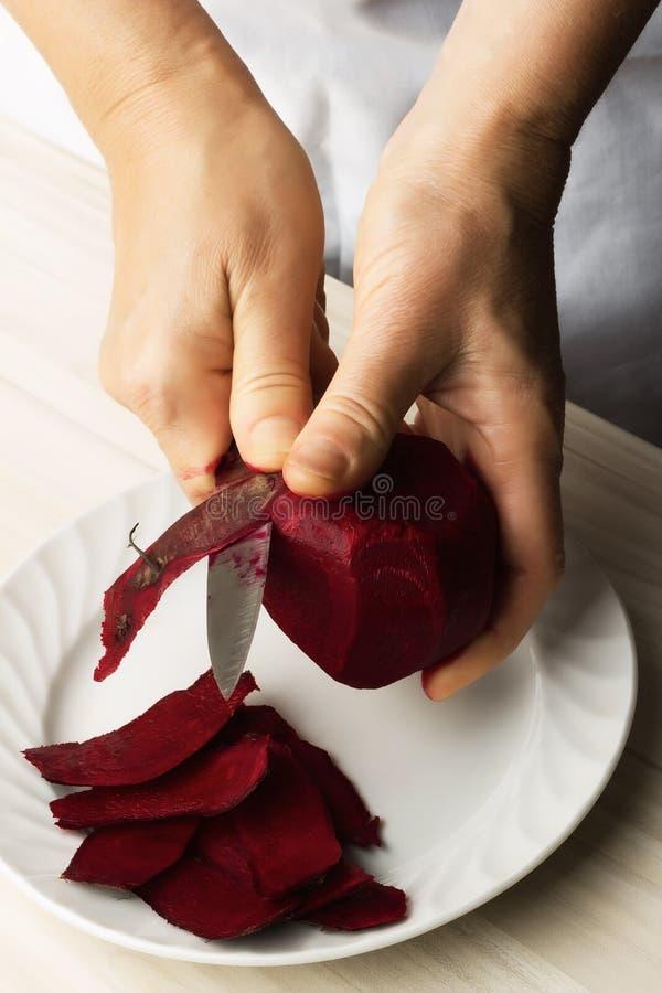 El cocinero de la mujer prepara remolachas imagenes de archivo